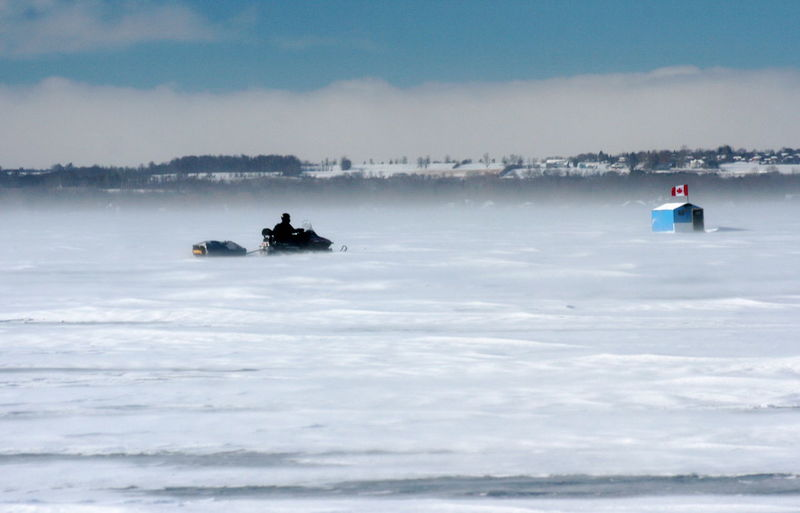 Person ice fishing in frozen lake during winter