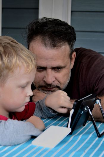 Watching the news Casual Clothing Childhood Countryside Elementary Age Fatherhood Moments Headshot Holding Leisure Activity Lifestyles Outdoors Person Tablet The Tablet Togetherness Internet Addiction