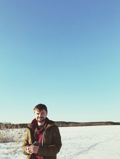 Portrait Of Man Standing On Snow Covered Field Against Clear Blue Sky