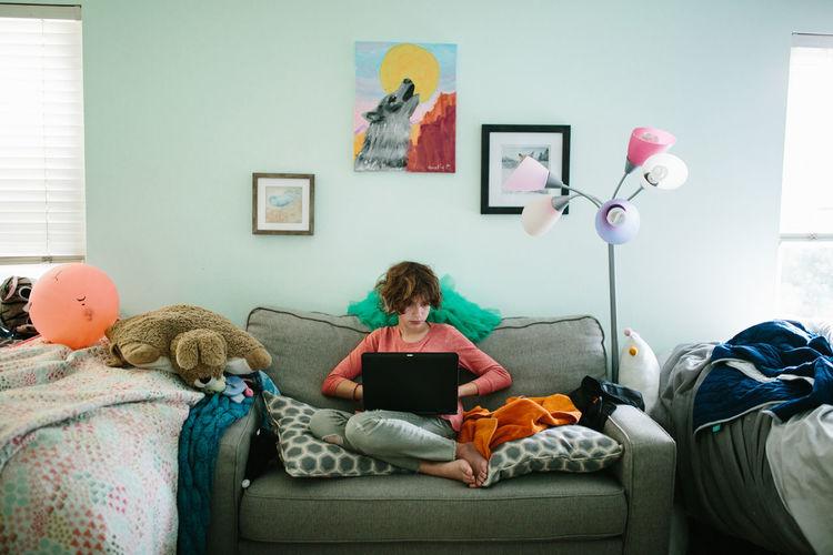 Boy sitting on sofa at home