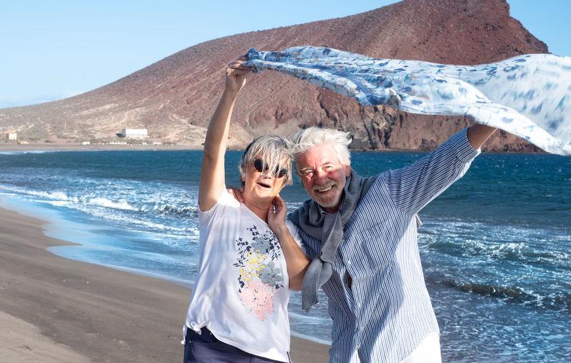 Senior couple holding scarf at beach
