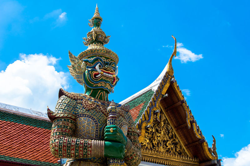 Low angle view of demon statue at grand palace against sky