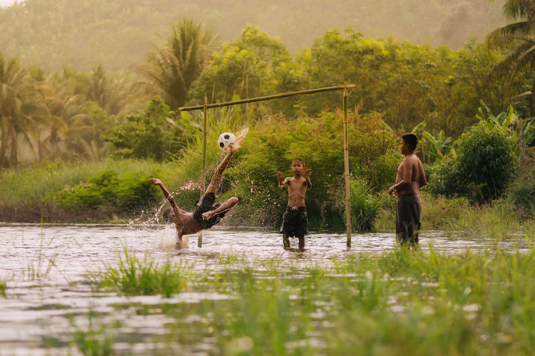 Children playing football in the river,Asia's rural lifestyle and nature. Animal Wildlife Animals In The Wild Day Fishing Lake Leisure Activity Males  Men Nature Outdoors People Plant Real People Reflection Standing Tree Vertebrate Water
