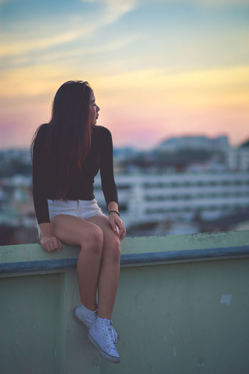 Woman Sitting On Railing During Sunset