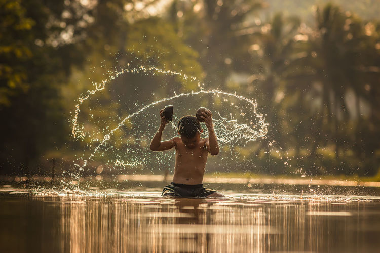 Children playing in the river at rural . Beauty In Nature Boys Day Fun Leisure Activity Lifestyles Long Exposure Motion Nature One Person Outdoors Real People Reflection Refreshment Shirtless Splashing Spraying Standing Sunlight Tree Water Waterfront Wet Young Adult