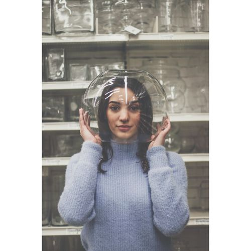 Portrait Of Young Woman Head In Glass Container Against Shelf