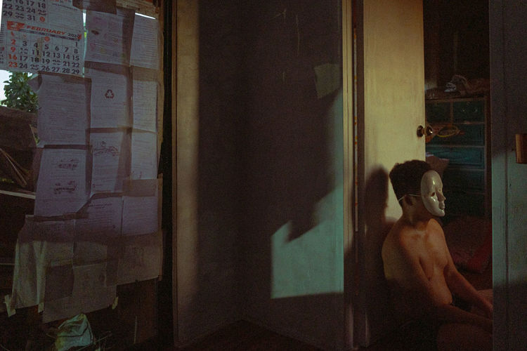 Rear view of shirtless woman standing by window