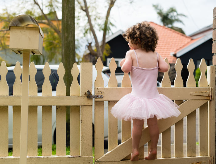 Rear View Of Girl Standing By Fence At Yard