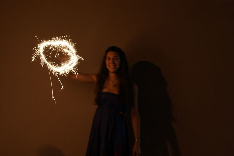 Portrait of woman holding illuminated sparkler against wall at night