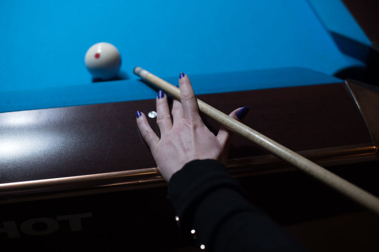 Cropped hand of woman playing snooker