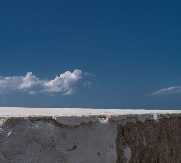 White Painted Retaining Wall Against Sky During Sunny Day