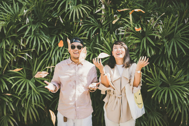 Cheerful young couple standing against plants