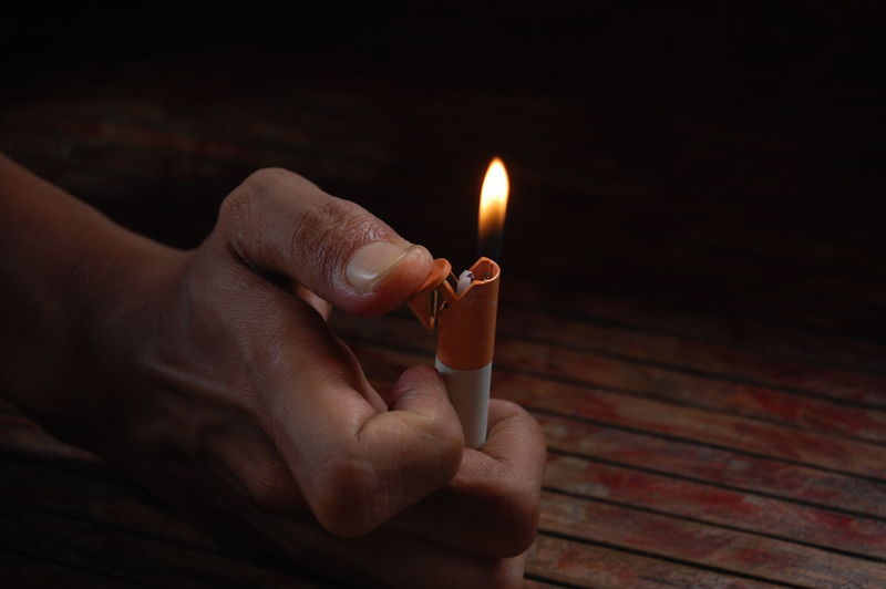 Cropped hand holding illuminated cigarette lighter