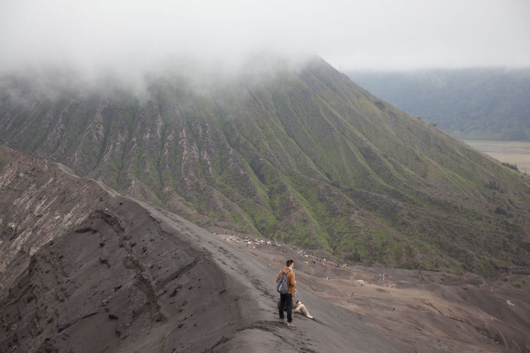 High Angle View Of Man Standing On Volcanic Mountains