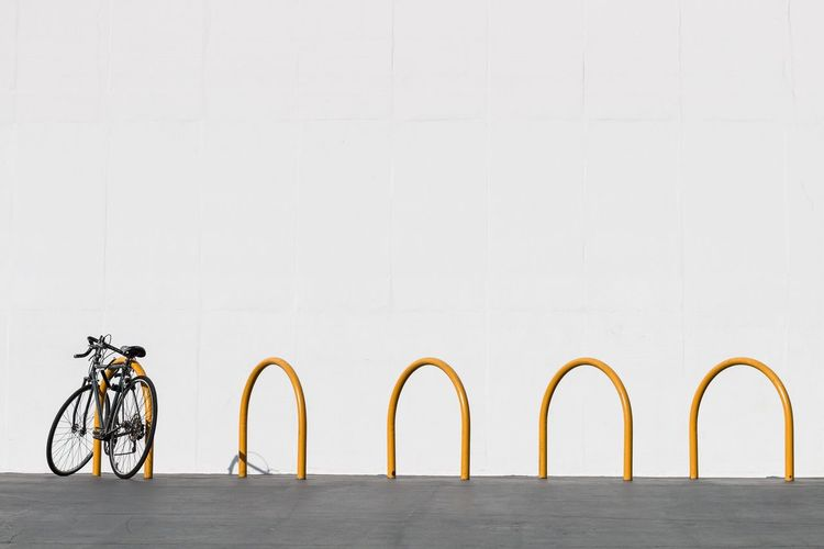 Bicycle Parker In Rack Against White Wall