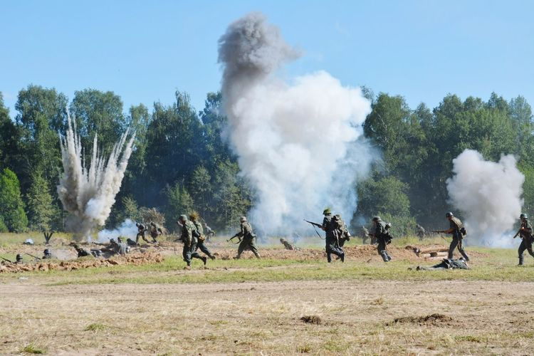Army soldiers running by explosion on field