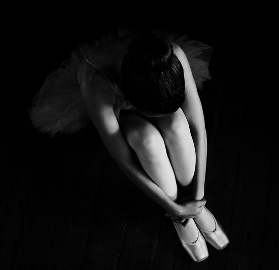 High angle view of ballet dancer sitting over black background