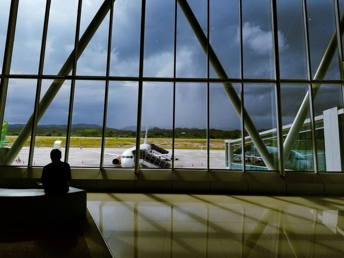 People on airport seen through glass window