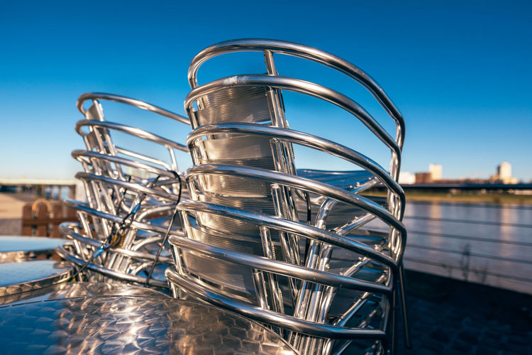Alloy chairs stapled wait for their first use at the rine promenade with dark blue sky Sky Water Clear Sky Metal Blue Nature No People Day Architecture Close-up Focus On Foreground Built Structure Reflection Outdoors Connection Sunlight Stainless Steel  Low Angle View Food And Drink Steel Silver Colored