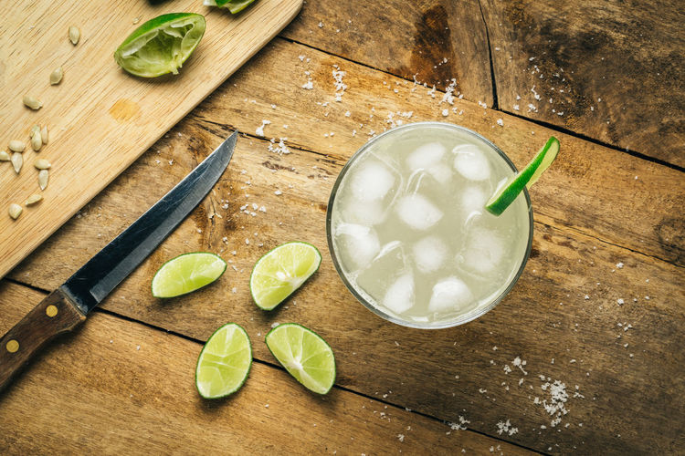 Cold fresh lime soda with lime slice on wooden background Close-up Cutting Board Day Drink Food Food And Drink Freshness Healthy Eating High Angle View Indoors  Leaf Lime Mojito No People Preparation  Ready-to-eat Refreshment SLICE Sour Taste Table Vegetable Wood - Material