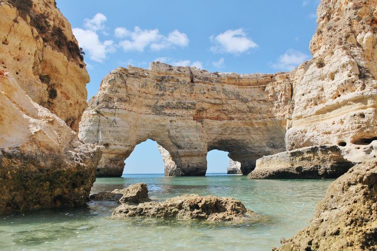Scenic View Of Stack Rock At Praia Da Marinha Against Sky