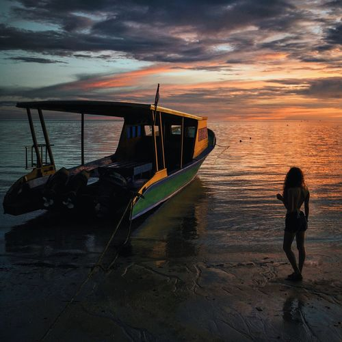 Rear view of young woman standing by boat at shore during sunset