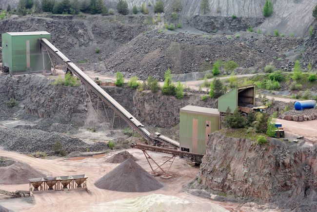 stone crusher in a quarry. mining industry Surface Mine Transportation Stone Pit Production Construction Materials Construction Material Steinbruch Rocks Stonepit Quarry Rock Quarry Mining Minerals Mine Loading Conveyor Belt Stone Crusher Steinbrecher