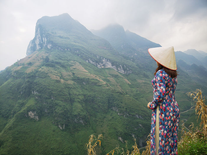 Side view of woman wearing asian style conical hat looking at mountains