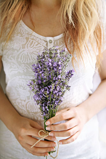 Midsection Of Woman Holding Lavender Flower