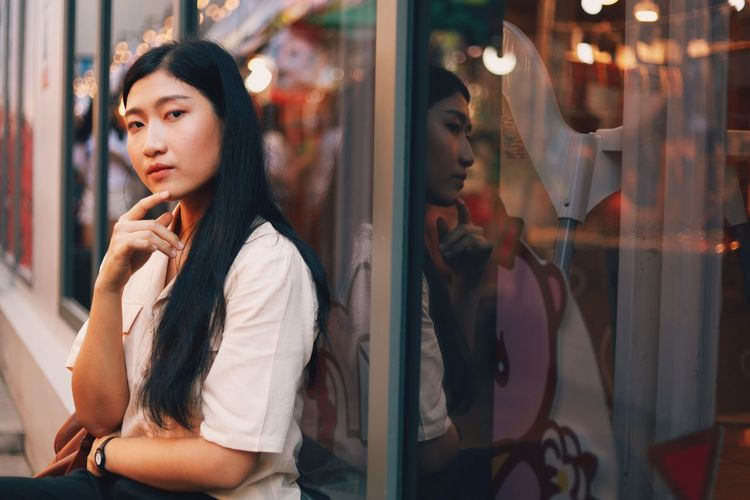One Person Young Adult Real People Lifestyles Window Reflection Young Women Leisure Activity Glass - Material Store Hair Looking Looking Away Transparent Hairstyle Casual Clothing Waist Up Contemplation Retail Display Outdoors Beautiful Woman