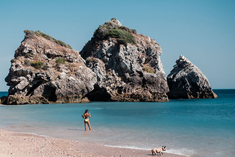 Beach Beauty In Nature Blue Clear Sky Cliff Day Full Length Geology Men Mountain Nature One Person Outdoors People Real People Rock - Object Rock Formation Scenics Sea Shirtless Sky Tranquility Vacations Water