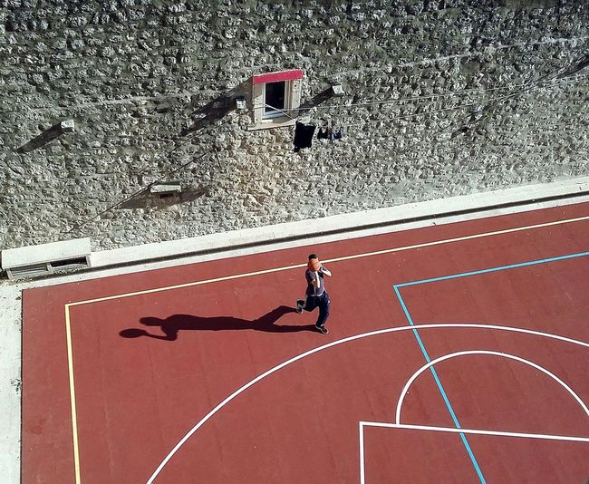 High Angle View Of Man Playing Basketball Against Wall