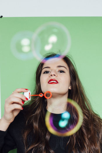 Portrait Of Young Woman Blowing Bubbles Against Green Background