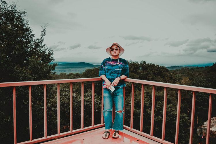 Portrait of boy standing on railing against sky