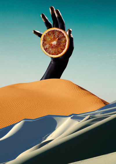 Digital composite image of cropped hand holding citrus fruit at desert against clear blue sky