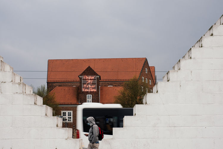Rear view of people on building wall against sky