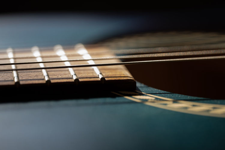 Close-up of guitar on table against black background