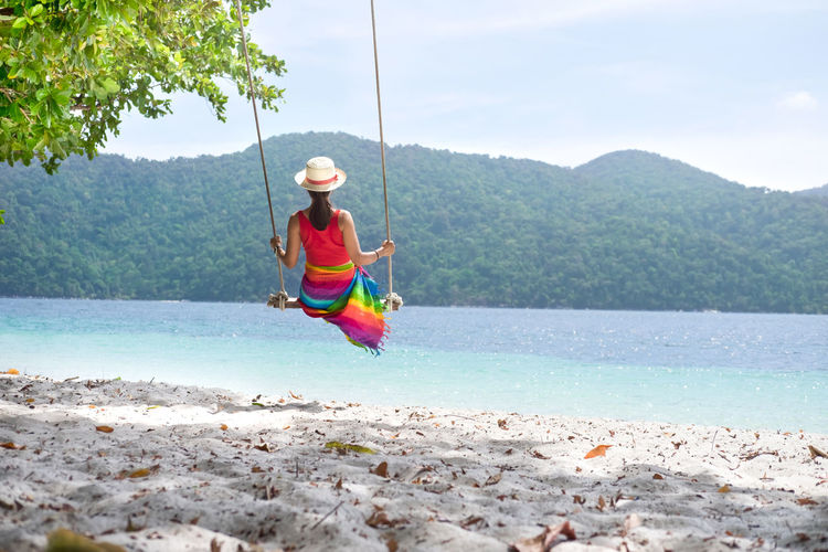 Rear view of woman sitting on rope swing at beach against sky