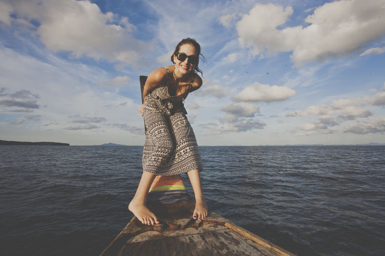 Full length of young woman bending on longtail boat in sea against sky