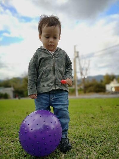 Low angle view of cute baby boy with ball standing on grassy field