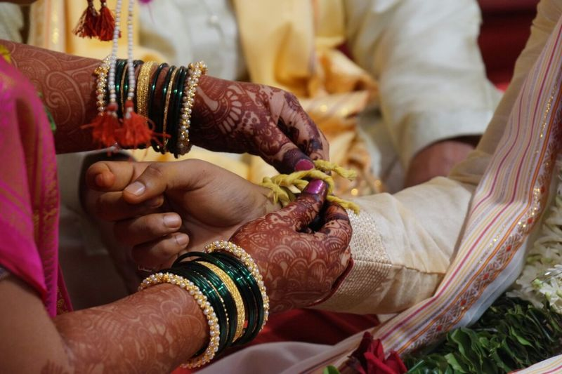 Cropped Hands Of Bride Tying Thread On Bridegroom During Wedding Ceremony