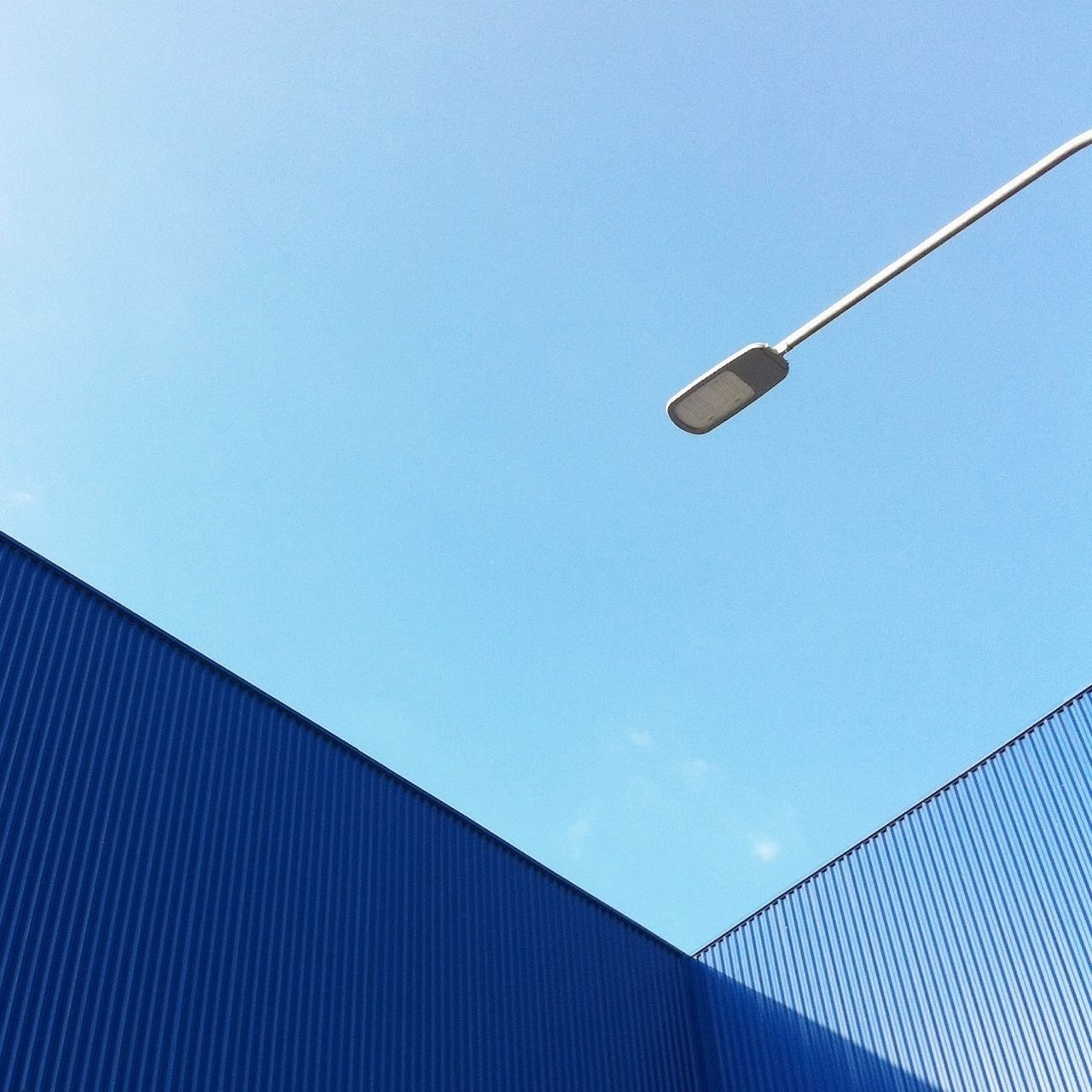 Low angle view of cargo containers and lighting equipment against sky
