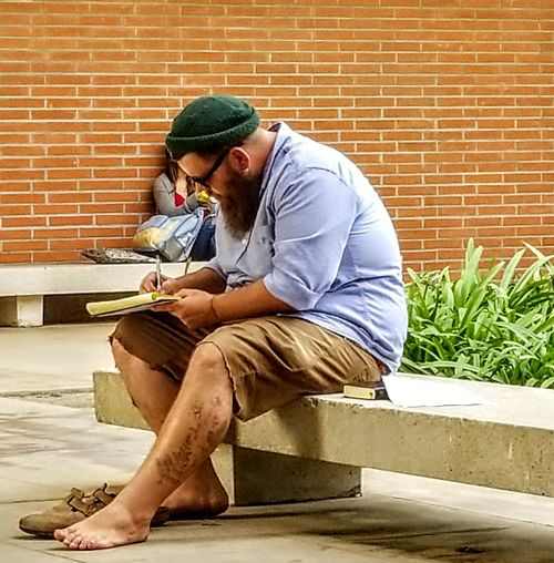 students on break Only Men One Man Only One Young Man Only Looking Down Young Adult Brick Wall Sitting