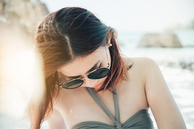 Close-Up Of Woman Wearing Sunglasses At Beach