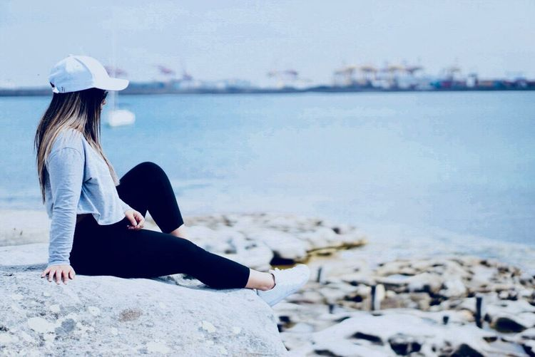 Sitting Relaxation Water Full Length Day Lake Rock - Object Casual Clothing Outdoors Focus On Foreground Women Leisure Activity One Person Nature Sky Beach Beauty In Nature Adult People