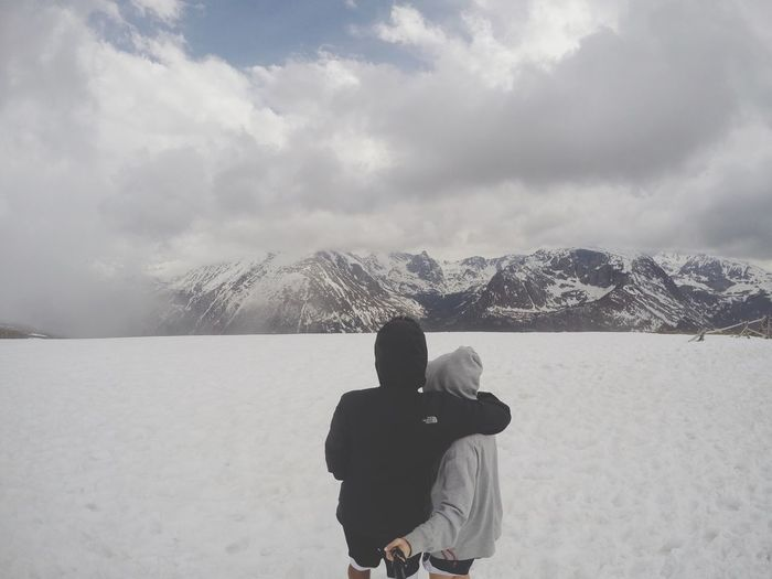 Rear view of couple photographing on snow covered field by mountains against cloudy sky