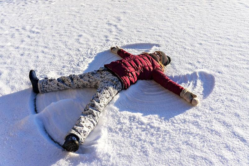 Young woman lying in the snow and making a snow angel. winter walks and fun, holidays