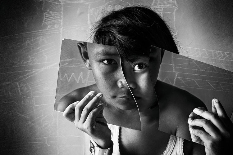 Portrait Of Girl Holding Broken Glass In Front Of Face With Reflection Of Boy At Classroom