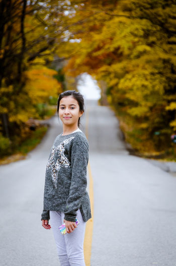 Portrait of cute girl standing on road during autumn