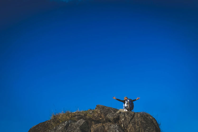 Low angle view of man standing on rock against clear blue sky